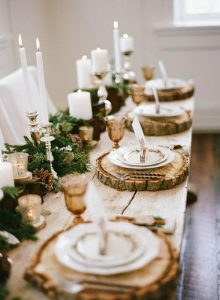 Rustic-winter-wedding-table-setting-with-candles-fresh-greens-and-pinecones